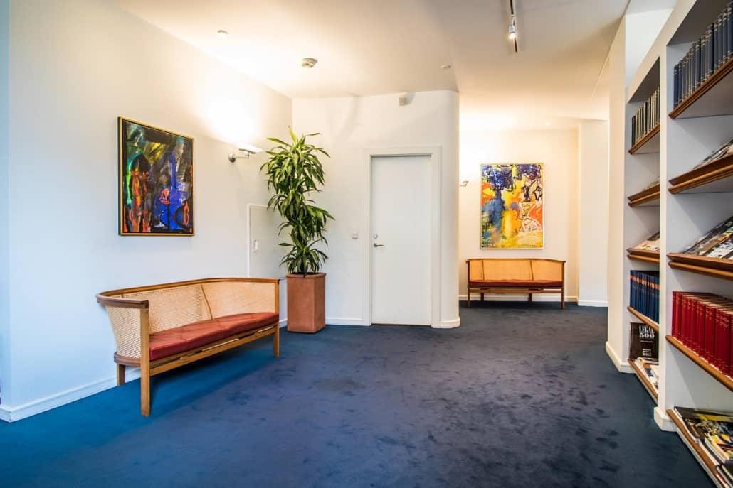 Venteværelse hos advokatfirma med blåt tæppe